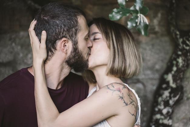 Jovem casal beijando debaixo de uma árvore subindo na parede Foto Premium