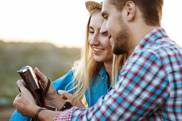 Jovem casal bonito de viajantes sorrindo, segurando a câmera antiga Foto gratuita