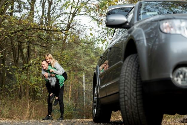 Jovem casal brincando atrás de um carro Foto gratuita