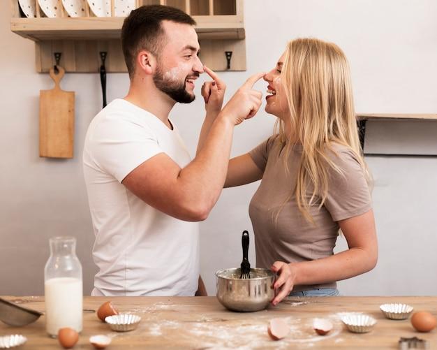 Jovem casal brincando com farinha na cozinha Foto gratuita