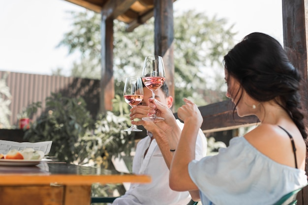 Jovem casal brindando com taças de vinho no jardim Foto gratuita
