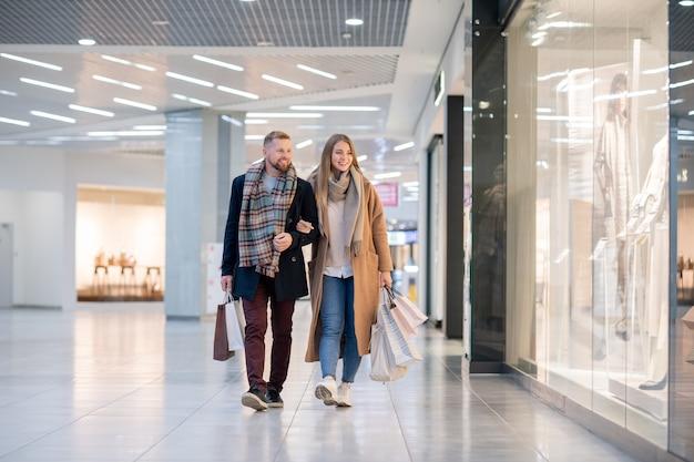 Jovem casal carinhoso em trajes casuais elegantes carregando sacolas de papel enquanto se move pelas vitrines do shopping Foto Premium