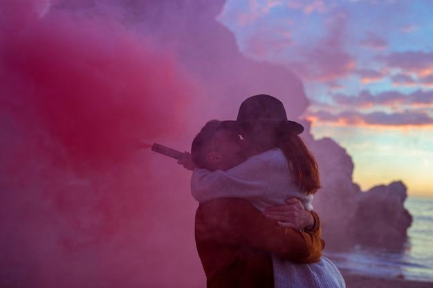 Jovem casal com bomba de fumaça beijando na beira-mar Foto gratuita