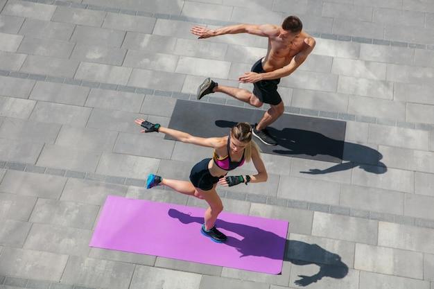 Jovem casal com roupa esportiva, fazendo exercícios matinais ao ar livre. Foto gratuita