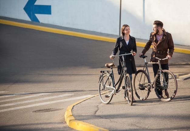 Jovem casal com uma bicicleta em frente à cidade Foto gratuita