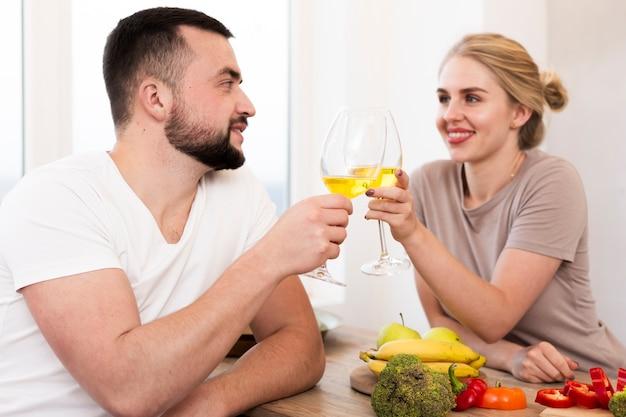 Jovem casal comendo legumes e bebendo juntos Foto gratuita
