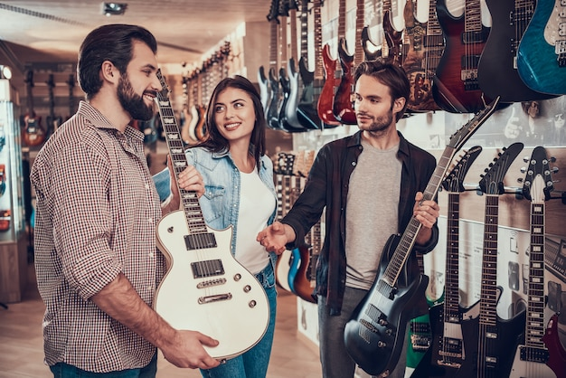 Jovem casal compra nova guitarra elétrica na loja de música Foto Premium