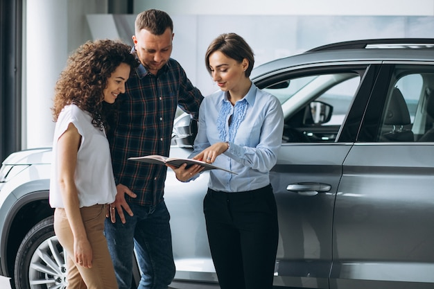 Jovem casal conversando com uma pessoa de vendas em um showroom de carros Foto gratuita