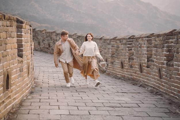 Jovem casal correndo e girando na grande muralha da china Foto gratuita