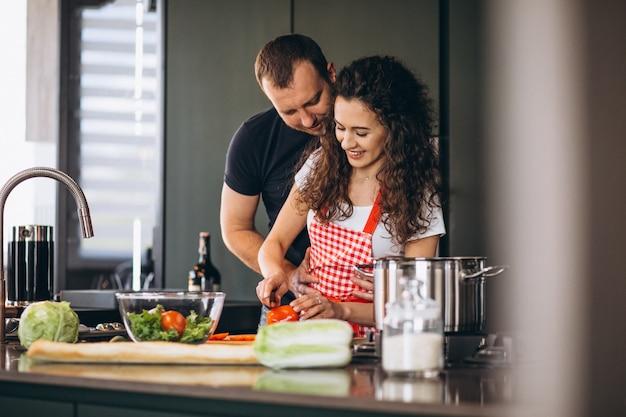 Jovem casal cozinhando na cozinha Foto gratuita