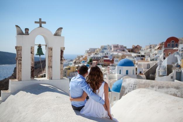 Jovem casal de lua de mel na ilha mais romântica santorini, grécia Foto Premium