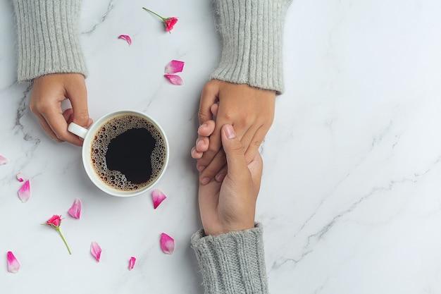Jovem casal de mãos dadas para comer café em uma mesa de madeira. Foto gratuita