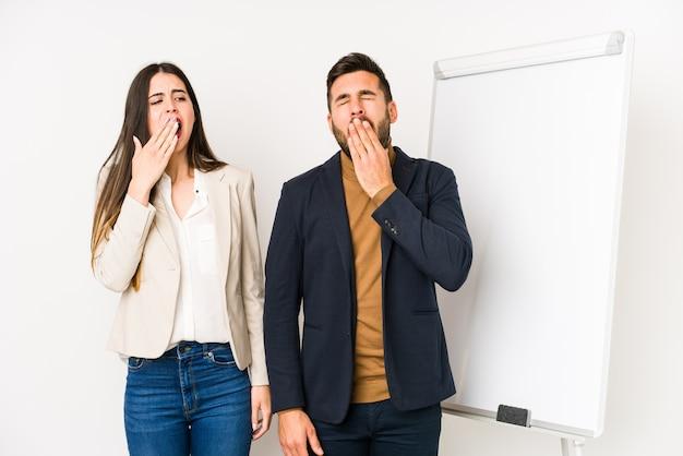 Jovem casal de negócios caucasiano isolado bocejando mostrando um gesto cansado, cobrindo a boca com a mão. Foto Premium