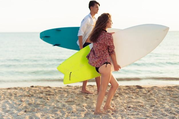 Jovem casal de surfistas Foto Premium