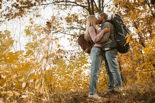 Jovem casal de turistas beijando na floresta ao ar livre Foto Premium