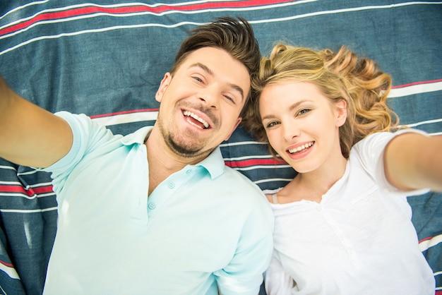 Jovem casal deitado no gramado do parque e fazendo selfie. Foto Premium