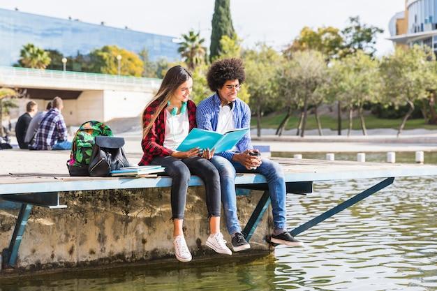 Jovem casal diverso está aprendendo juntos sentado do lado de fora no parque Foto gratuita