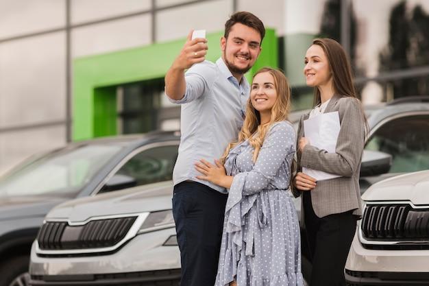 Jovem casal e negociante de carro tomando uma selfie Foto gratuita