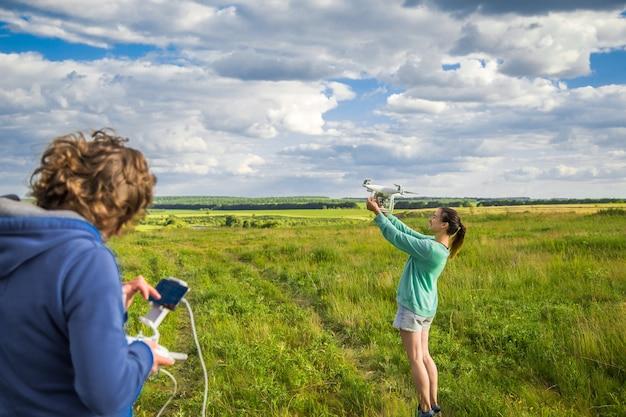 Jovem casal em um campo lança o drone para o céu Foto gratuita