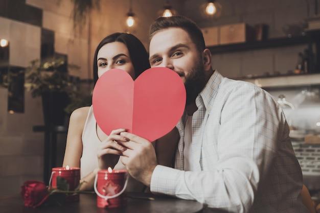 Jovem casal encantador esconde por trás do coração de papel Foto Premium