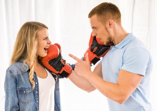 Jovem casal está brigando e usando luvas de boxe. Foto Premium