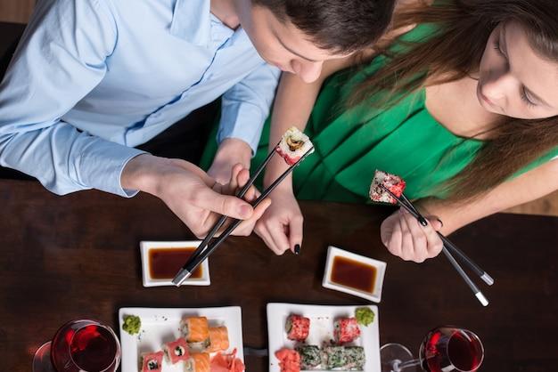 Jovem casal está comendo sushi no restaurante. Foto Premium
