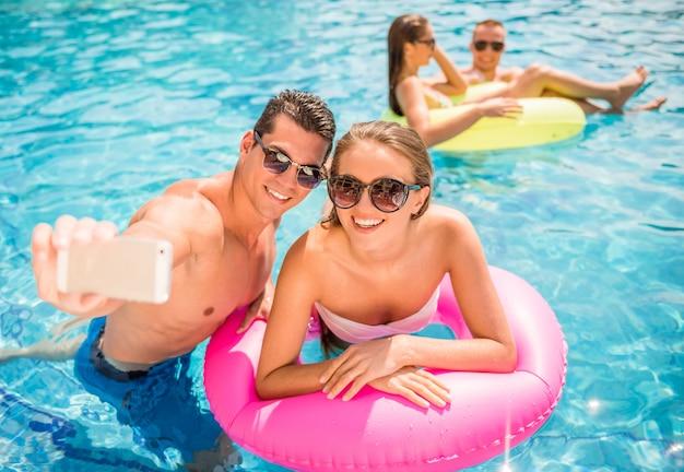 Jovem casal está fazendo selfie enquanto se diverte na piscina. Foto Premium