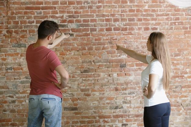 Jovem casal fazendo conserto de apartamento juntos. homem e mulher casados fazendo reforma ou reforma em casa Foto gratuita