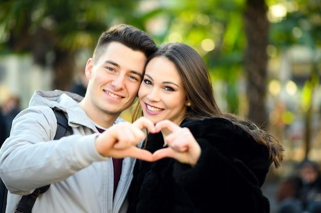 Jovem casal fazendo formato de coração com as mãos Foto Premium