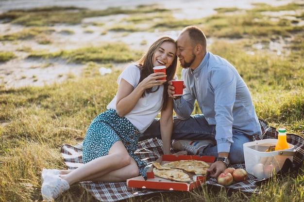 Jovem casal fazendo piquenique com pizza no parque Foto gratuita