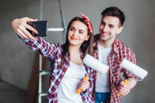 Jovem casal fazendo reparos no apartamento e tirando fotos de si mesmo no telefone Foto Premium