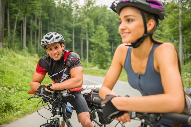 Jovem casal feliz andando de bicicleta na estrada da floresta. Foto Premium