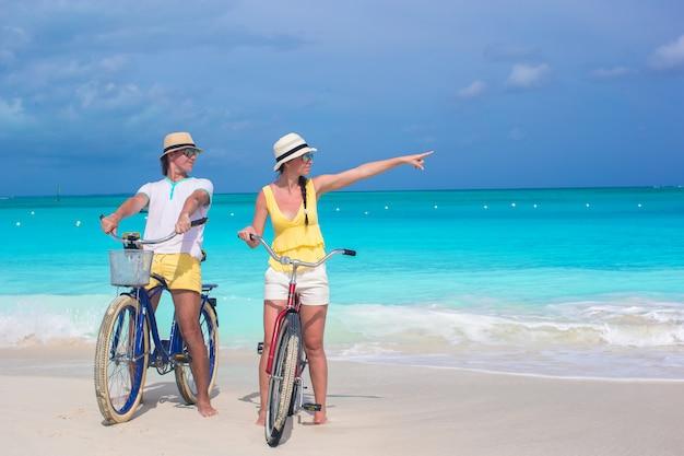 Jovem casal feliz andando de bicicleta na praia tropical branca Foto Premium