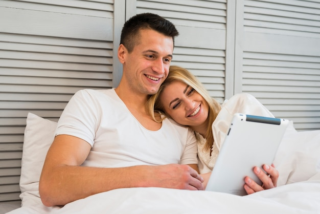 Jovem casal feliz com tablet sob o cobertor na cama Foto gratuita