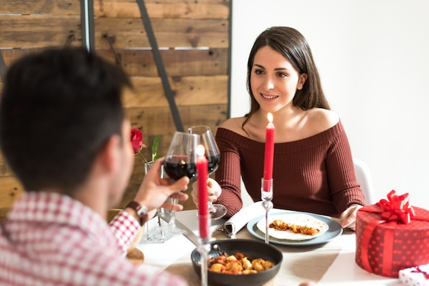 Jovem casal feliz comemorando o dia dos namorados com um jantar em casa bebendo vinho, felicidades. Foto Premium