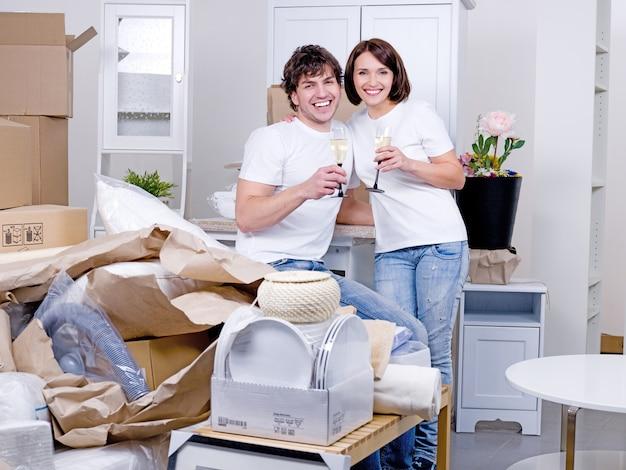 Jovem casal feliz comemorando seu novo lar com uma taça de champanhe - dentro de casa Foto gratuita
