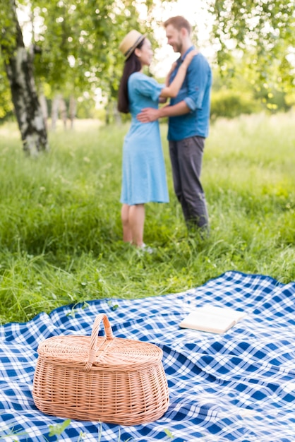 Jovem casal feliz dançando no piquenique na natureza Foto gratuita