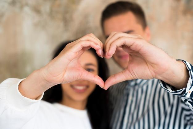 Jovem casal feliz gesticulando coração com as mãos Foto gratuita