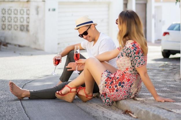 Jovem casal feliz no amor caminha pelas pequenas ruas em espanha, beber champanhe, rir. vacatio Foto gratuita