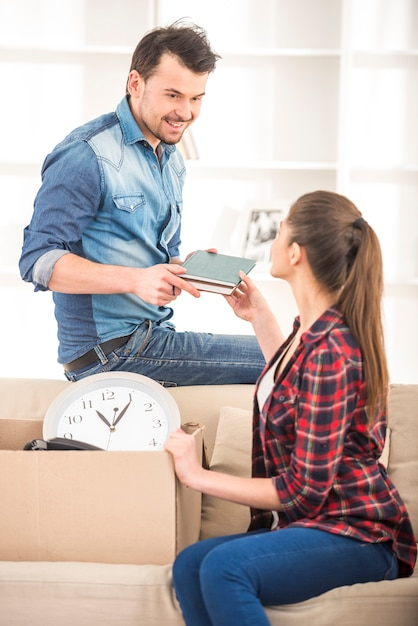 Jovem casal feliz organizando o apartamento. Foto Premium