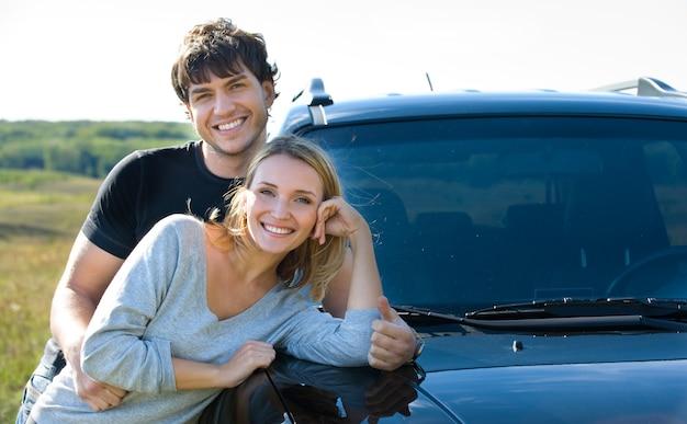 Jovem casal feliz parado perto do carro Foto gratuita