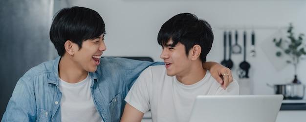 Jovem casal gay beijando enquanto estiver usando o laptop do computador em casa moderna. os homens asiáticos lgbtq felizes relaxam o divertimento usando a tecnologia jogam mídias sociais juntos enquanto sentam a mesa na cozinha em casa. Foto gratuita