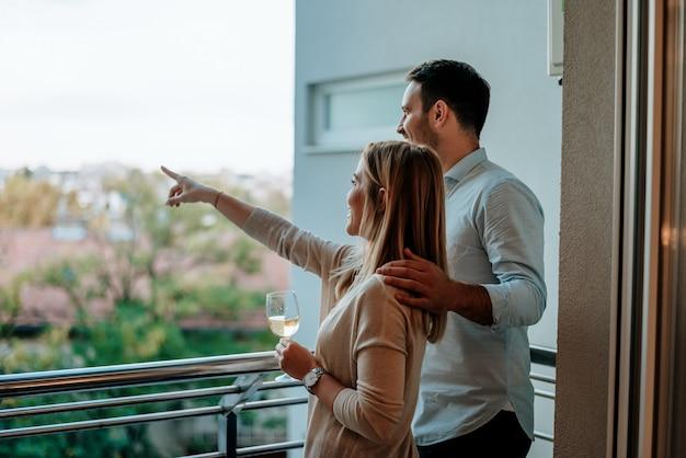 Jovem casal gosta de beber vinho na varanda. mulher apontando algo. Foto Premium