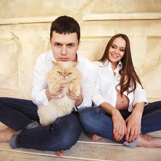 Jovem casal grávida com gato Foto Premium