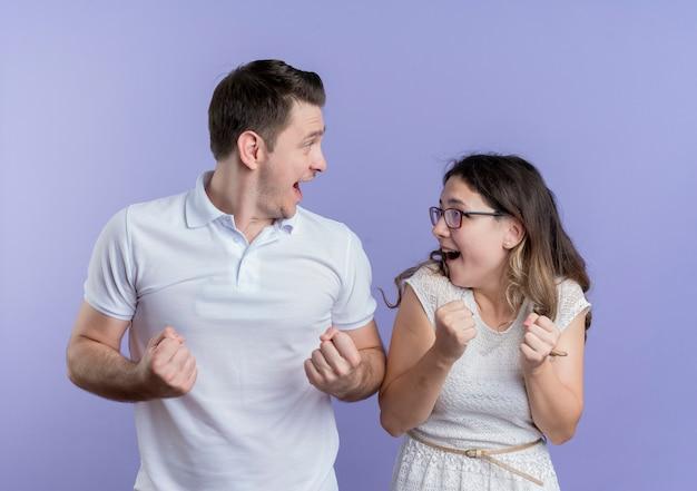 Jovem casal, homem e mulher, cerrando os punhos felizes e animados em pé sobre a parede azul Foto gratuita