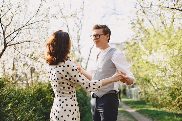 Jovem casal homem e mulher em um jardim florescendo Foto gratuita