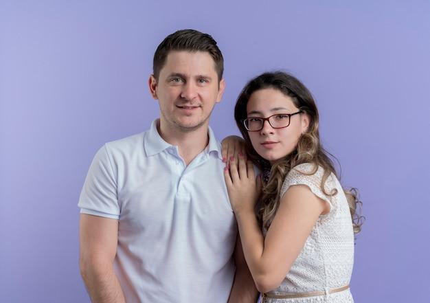 Jovem casal, homem e mulher, juntos, felizes e apaixonados, perto de uma parede azul Foto gratuita