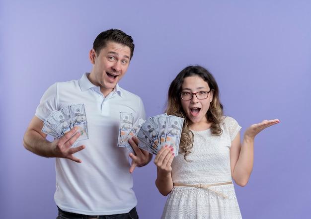 Jovem casal, homem e mulher segurando dinheiro, felizes e surpresos, de pé juntos sobre a parede azul Foto gratuita