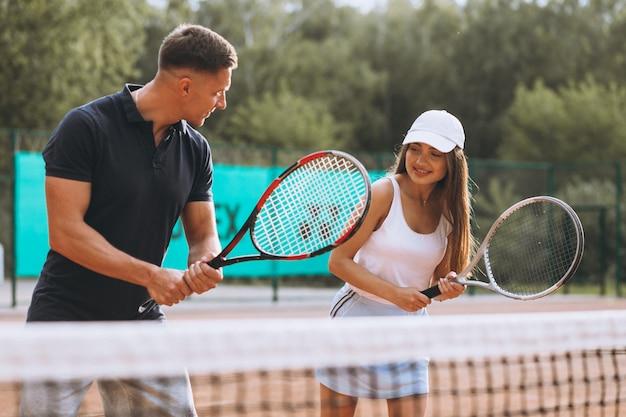Jovem casal jogando tênis na quadra Foto gratuita