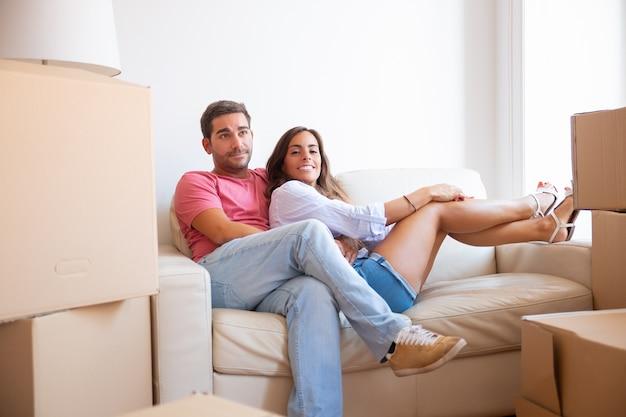 Jovem casal latino alegre sentado no sofá entre pacotes de papelão no apartamento novo, Foto gratuita